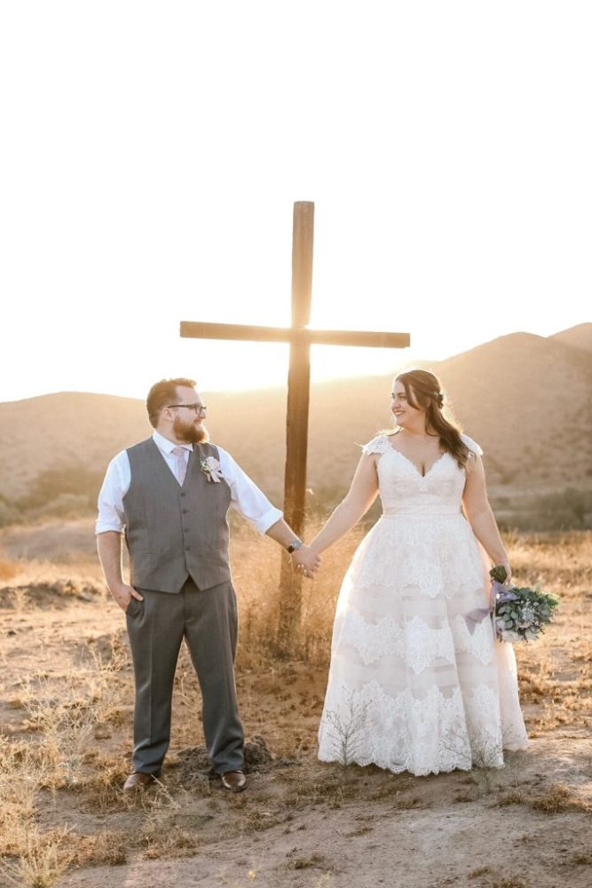 curvy bride in plus size two-tone lace ballgown wedding gown holding her groom's hand in front of a cross in the desert.