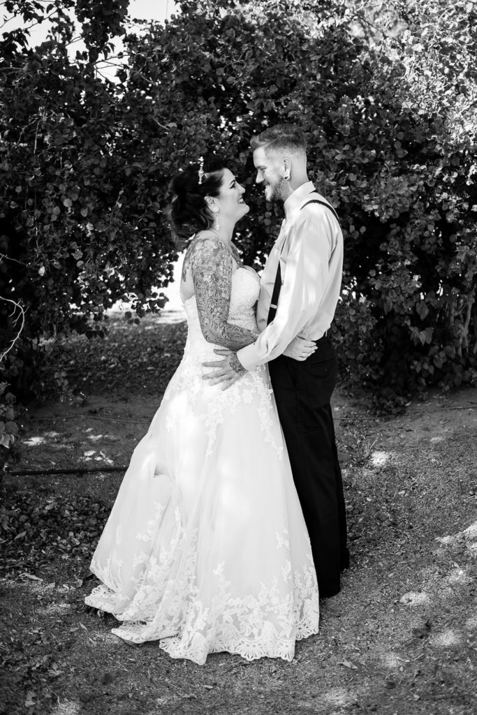 black and white tattooed curvy bride looking at her husband