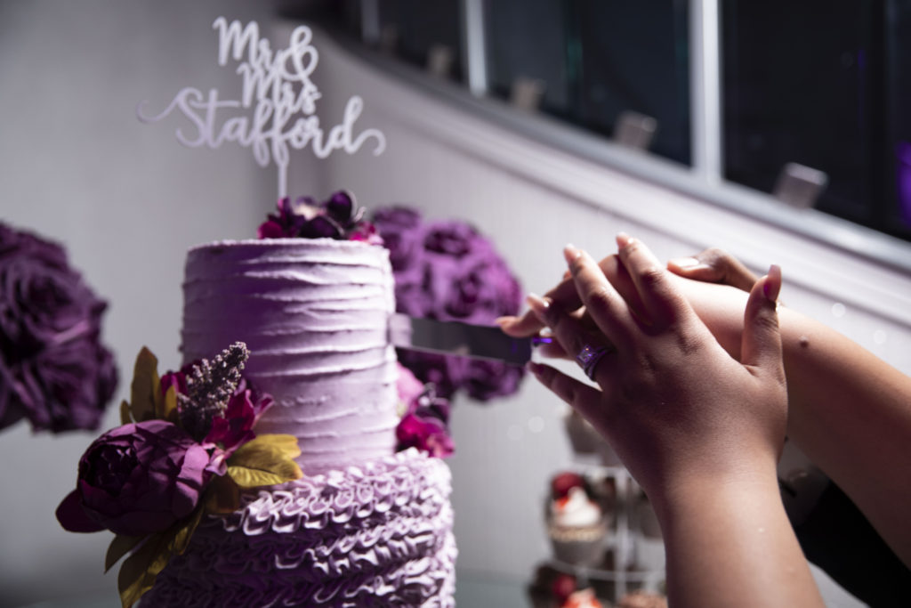 cutting the cake, which is purple