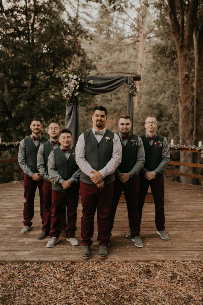 Groomsmen in vests and maroon pants.