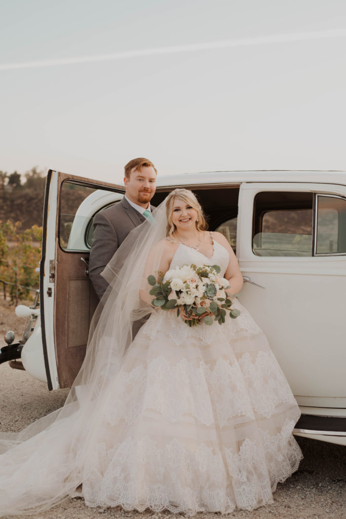 newlyweds in front of vintage car plus size bride