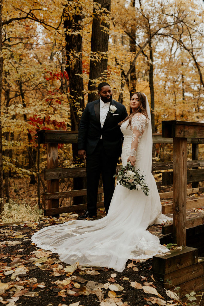 newlyweds in woods on bridge with cathedral veil