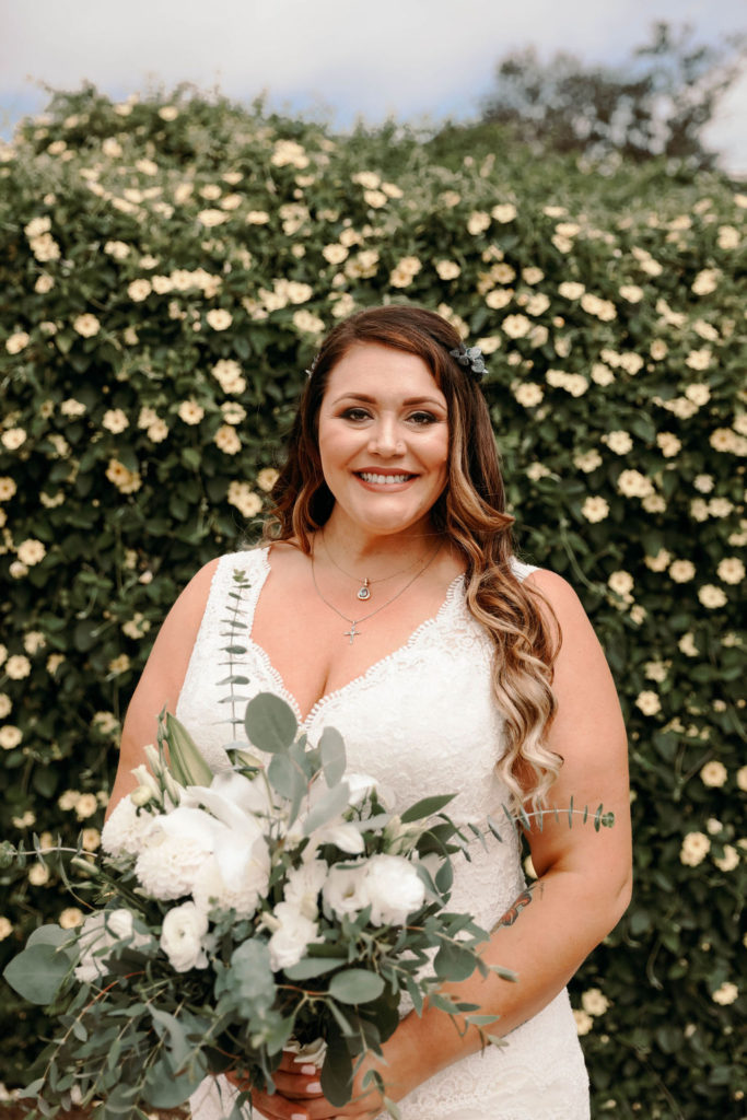 plus size bride wearing vneck lace wedding dress with greenery behind her and carrying a large wedding bouquet